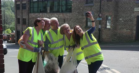 A group of five mature adults, wearing high visibility jackets, as they take a selfie together.