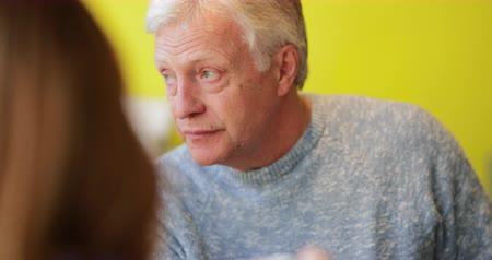 A close up shot of a mature man talking with friends in a cafe.