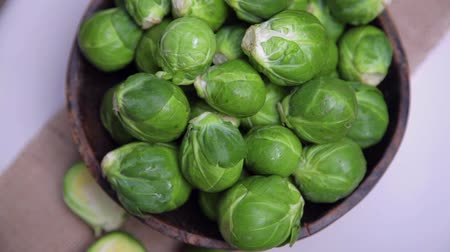 macrobiotic : Brussels sprouts in wooden bowl rotating on white Stock Footage