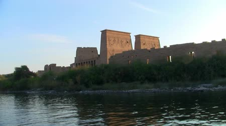 imparatorluk : Cruising by the Ancient Egyptian Temple of Philae on Agilika Island in Aswan, Egypt on a Sunny Day Stok Video