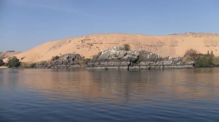 nílus : Sand Dune and Grey Rocks Adjacent to the Water of the River Nile in Egypt on a Sunny Day Stock mozgókép