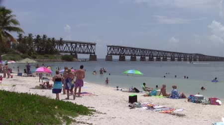 Bahia Honda, Florida, United States - Circa July 2013: People bathing in the summer at Bahia Honda Beach with the old and defunct Bahia Honda Railroad Bridge in the background.