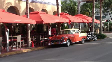 sul : Miami, Florida, USA - Circa July 2013: Orange Oldtimer Car on Ocean Drive in Miami Beach, Florida, United States, Parked in Front of I Paparazzi Bar with Orange Parasols