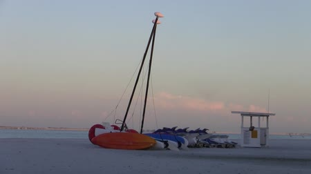 Red Catamaran Sailboat at Sunset on a Beautiful Sandy Beach in Florida, United States with Lifeguard Tower