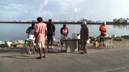 Marigot, Saint Martin - Circa July  2013: Professional Fish Cleaners Working and Gutting Fish at the Fish Market with Customers in Marigot, Saint Martin (Sint Maarten) in the Caribbean.