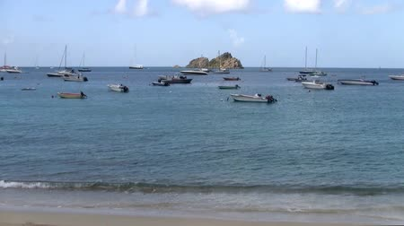 ancorado : Small Boats Anchored in a Caribbean Bay in Sint Maarten with a Small Island Stock Footage