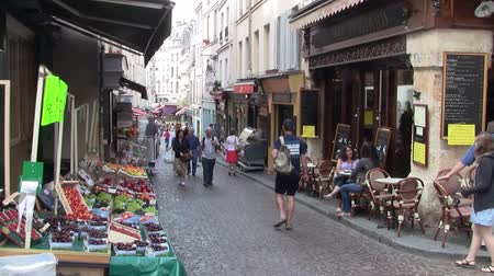 Paris, France - Circa July 2013: Market Stalls and a Cafe in the famous Rue Mouffetard on the Corner with Rue de Arbalete in Paris, France, with People Strolling on the Street. Stock Footage