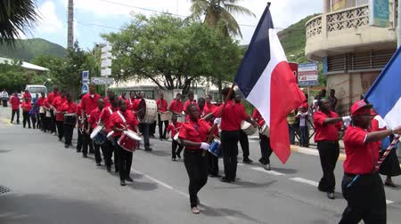 mais : Marigot, Saint Martin - July 14 2013: Creole band with Red Shirts and Drums at Parade on the 14th July, the French National Holiday in Marigot. Afro-Caribbean Musicians celebrating Bastille Day. Stock Footage
