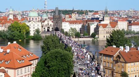 Charles Bridge in Prague Across River Vltava - Aerial View - Tourist Crowds Passing on a Hot Summer Day