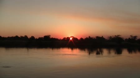 tourist silhouette : Romantic Sunset on the Okavango River with Beautiful Orang Colors in Namibia, Africa Stock Footage