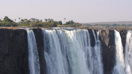 Victoria Falls Waterfall in Zimbabwe, Africa, a famous tourist destination and Unesco Natural World Heritage Site Stock Footage