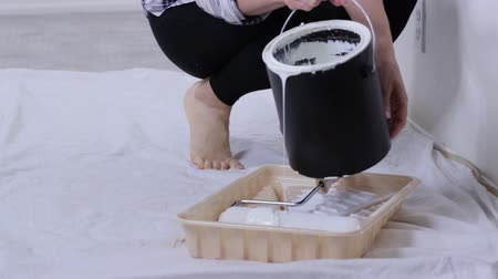 legs only : Wall painting preparation. Woman pours paint into the tray and dips roller Stock Footage