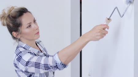 greater : Young woman painting wall in white
