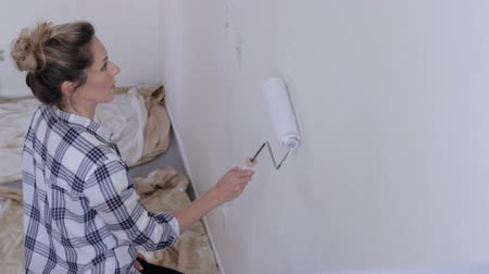 реальное время : Young woman painting wall in white with paint roller Стоковые видеозаписи