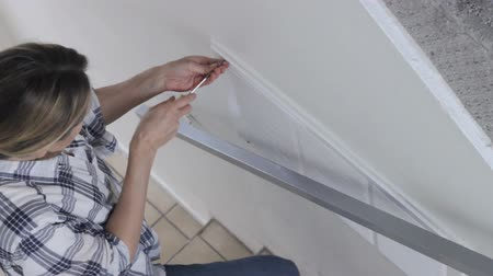 ev hayatı : Young woman using a screwdriver to remove screws out of air grill of the house ventilation system Stok Video
