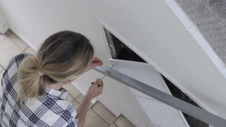 közepes : Young woman using a screwdriver to remove screws out of air grill of the house ventilation system Stock mozgókép