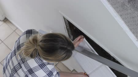 közepes : Young woman removing air grill from the house ventilation system