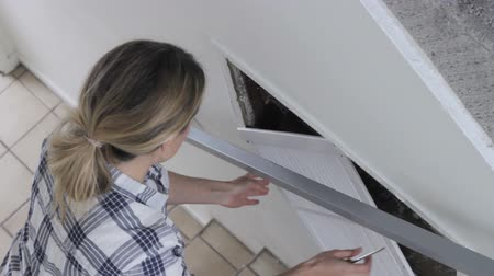 greater : High-speed footage of young woman using a screwdriver to remove screws out of air grill of the house ventilation system Stock Footage