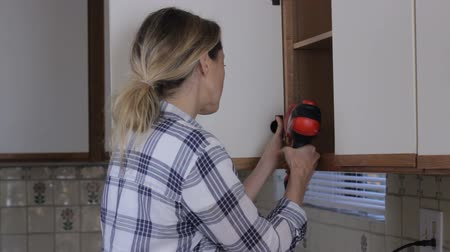 DIY woman fixing cabinet door with electric driver drill Wideo