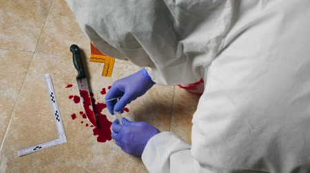 forgery : Expert Police takes blood sample from a blood knife at the scene of a crime, conceptual image