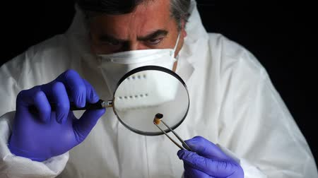 criminology : Expert Police examines a cigarette butt in ballistic laboratory with magnifying glass