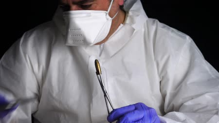 evidência : Expert Police examines a cigarette butt in ballistic laboratory with magnifying glass