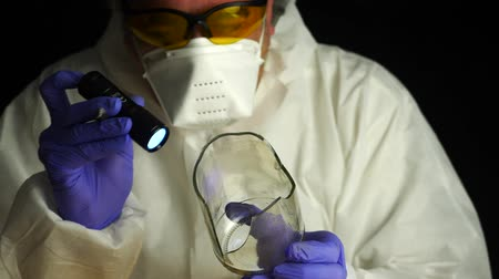 criminology : Expert Police get fingerprints from a broken glass bottle in Criminalistic Lab, conceptual image