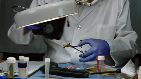 criminology : Scientific police examining and making photos of a bullet cap in ballistic Laboratory Stock Footage