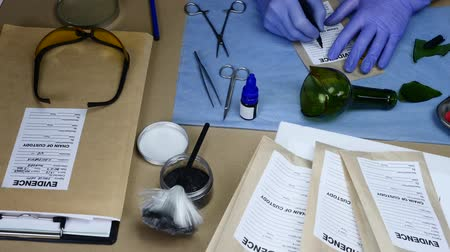 impressão digital : Scientific police officer examining sliced traces of crystal of a bottle in ballistic laboratory