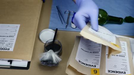 criminology : Scientific police officer examining evidence bags of tests labeled in ballistic laboratory