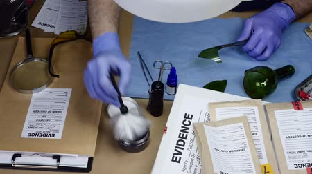 forgery : Scientific police officer examining sliced traces of crystal of a bottle in ballistic laboratory