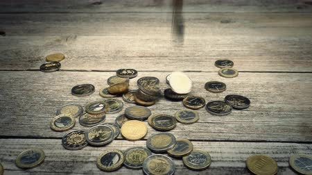 cash free : Coins falling on a pile on wooden table background. Studio shot. Stock Footage