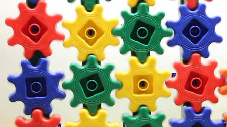 plastics : colorful plastic gears turning on a white background