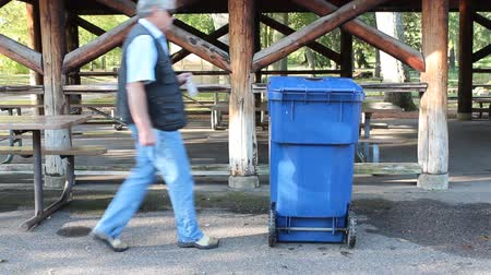 man places a plastic bottle into a recycle bin Wideo