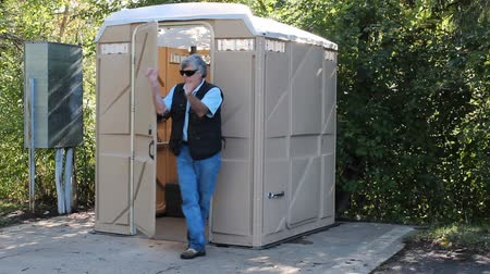 man exiting a foul smelling outhouse