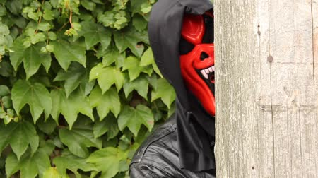 red devil mask looking around the corner of a building