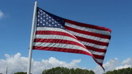 the United States flag waving against a blue sky