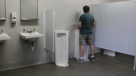 mature man using the urinal in a public restroom