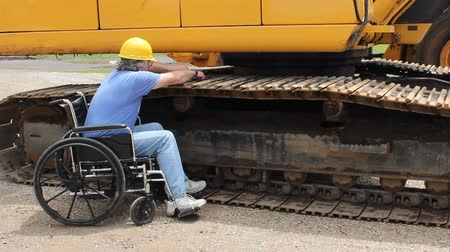 csavarkulcs : disabled maintenance mechanic working on the tracks of a large backhoe