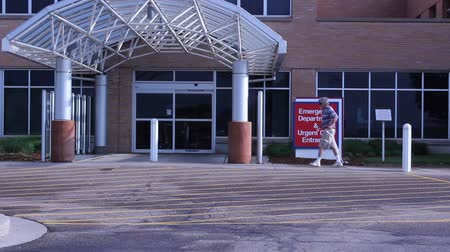 entrance : man with a cane walks into the emergency entrance of a hospital