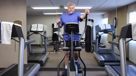 elliptical : mature man exercising on an eliptical machine
