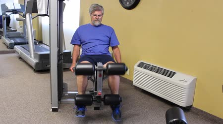 mature man working his legs on an excercise machine Wideo