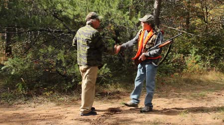 Two mature hunters meet on a wooded trail and exchange information