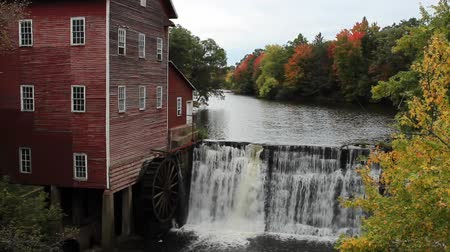 vintage grain mill next to the waterfall that provides power for processing