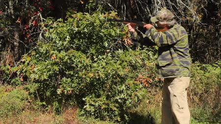 hunter in the Autumn woods aims his rifle at an Unknown target. Wideo