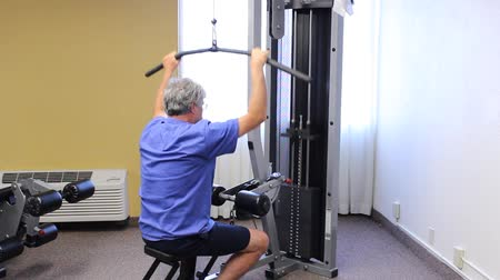 mature man using a resistance machine to stay in shape