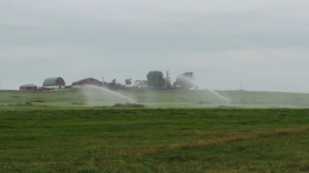 A large irrigation system with farm buildings in the background.