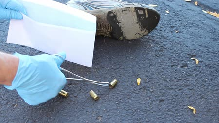 Investigator recovers empty shell cases from a crime scene.