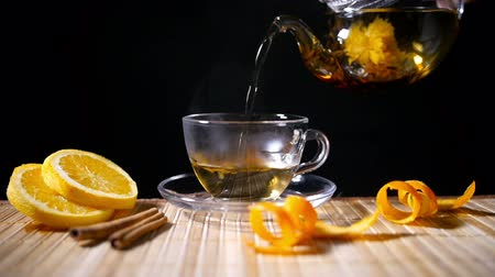 homeopatia : Pouring Blooming Tea with Cinnamon and Orange, slowmotion