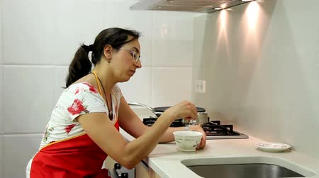 домохозяйка : Housewife making tea in the kitchen Стоковые видеозаписи